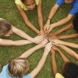 Unity - Top view of multi ethnic children lying with their hands together